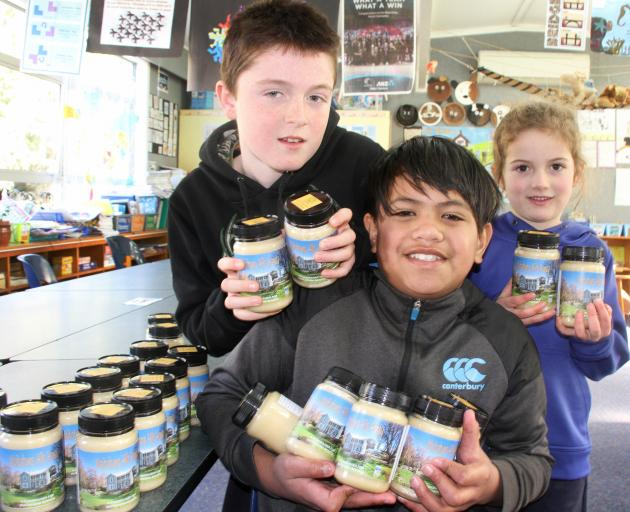 Waitahuna School pupils (from left) Lachie Wark (11), Waka Tuwhangai (11) and Ava Tweed (5) show off the school's Waitahuna Hills Honey, produced and marketed by the children as part of a school project. Photo: Jon Cosgrove