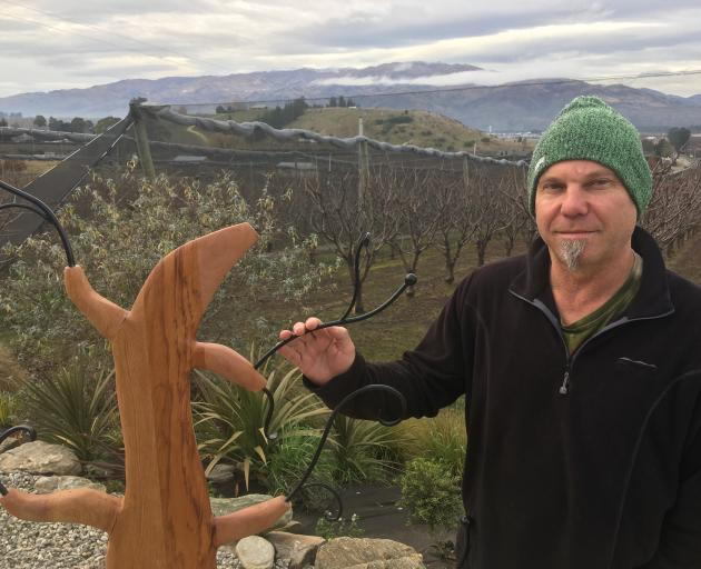 Sculptor Jim Ashe showcases one of his latest creations, made from recycled rimu bed frames. Photo: Alexia Johnston