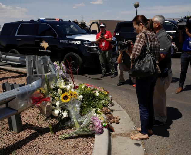 People look at flowers placed at the site of a mass shooting where 20 people lost their lives at a Walmart in El Paso. Photo: Reuters