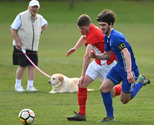 Mosgiel's Rory Findlay (in blue)  and Nomads United's Liam Thompson race for the ball during...