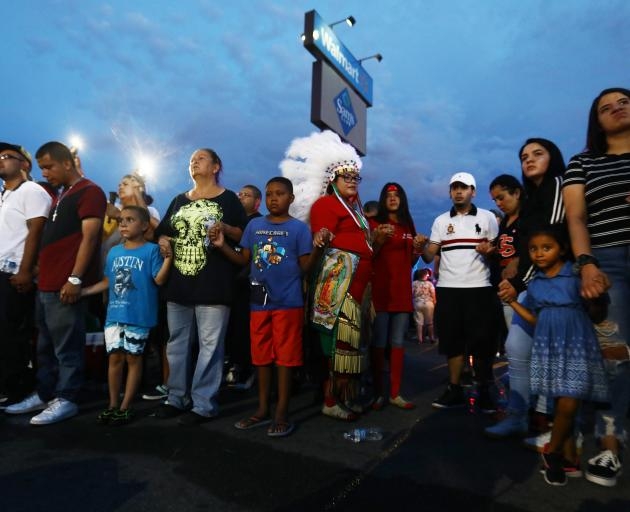 Children and adults gather outside the El Paso Walmart where a white supremacist gunman killed 22...