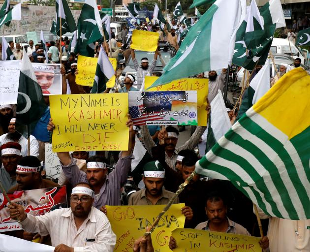 People hold flags and signs in solidarity with the people of Kashmir, during a rally in Karachi. Photo: Reuters