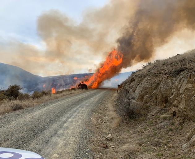 A vegetation fire jumps Meyers Pass Rd in the South Canterbury high country yesterday afternoon....