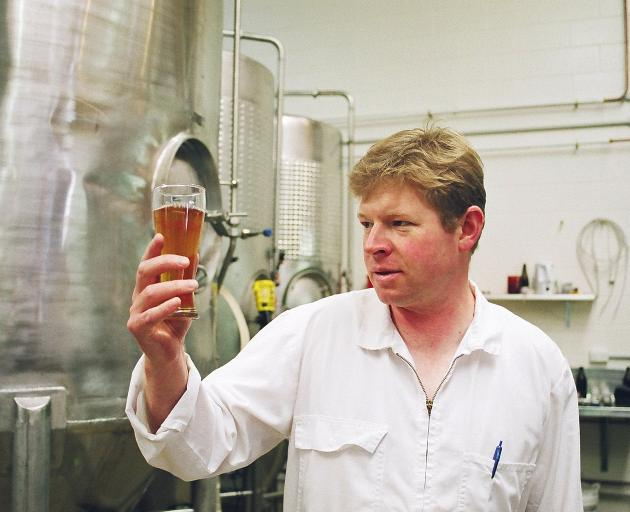 Richard Emerson checks the clarity of one of his early brews. Photo: Geoff Griggs