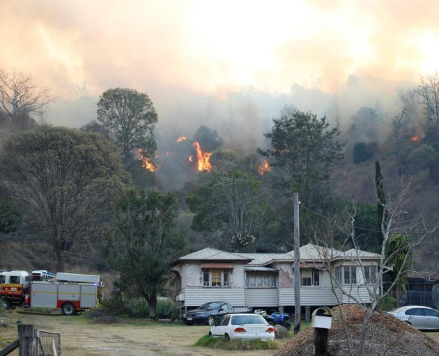 Fire and Emergency crew battle bushfire near a house in the rural town of Canungra in the Scenic...