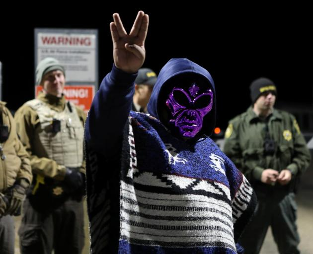 An attendee wears an alien mask at the gate of Area 51 as an influx of tourists responding to a...