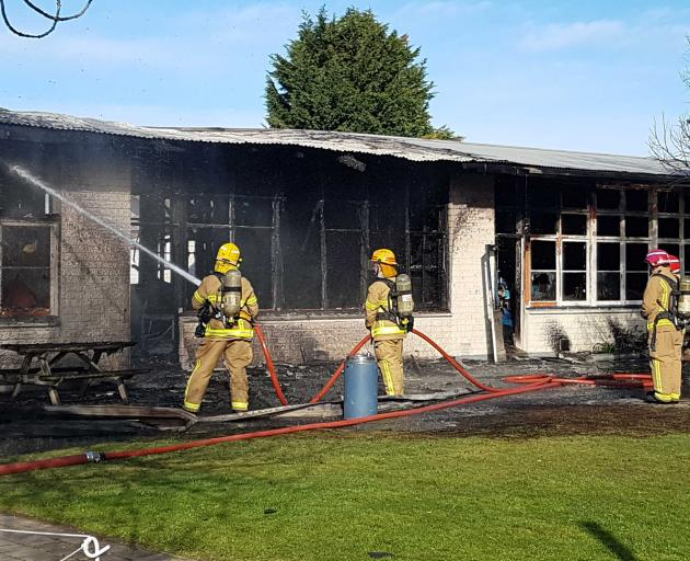 Firefighters dampen down the fire at Russley School. Photo: Geoff Sloan