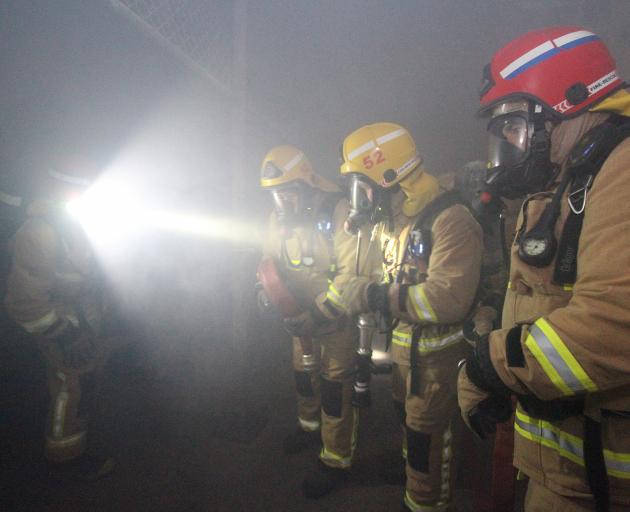 Firefighters work out their plan of attack inside a smoke-filled room.