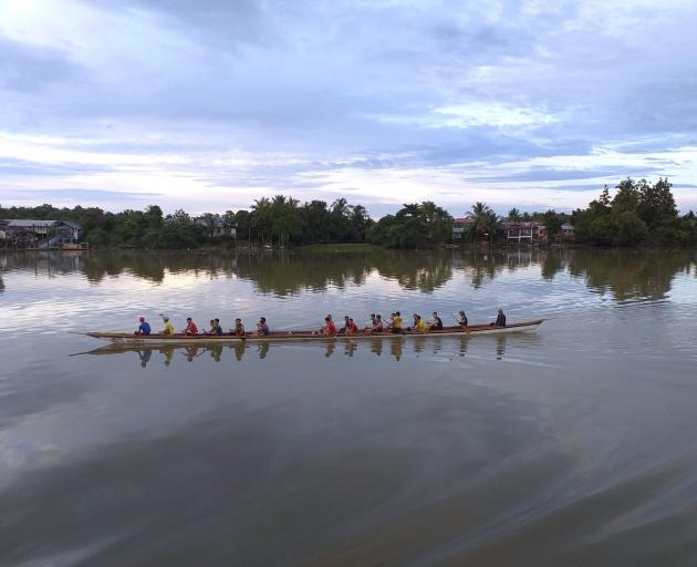 Dragon boats slice through the water on Sarawak River.