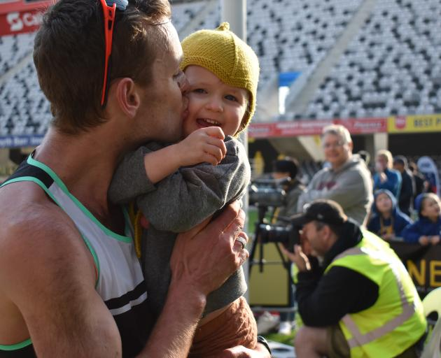 Inkster-Baynes kisses daughter Indi (3) after winning the national half marathon title.