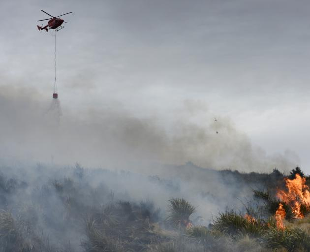 A helicopter drops water on to the Flagstaff fire in Dunedin yesterday.