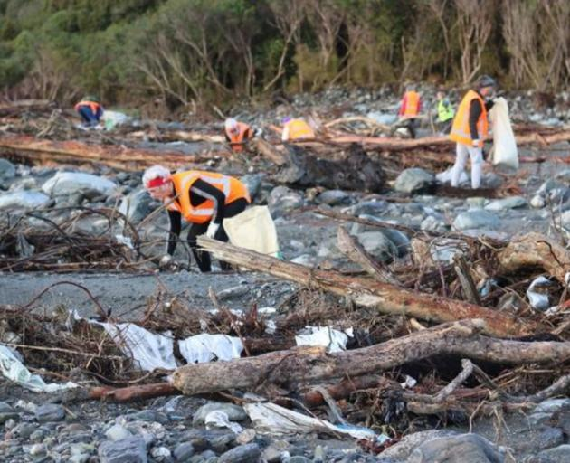 Volunteers pick up rubbish where a disused Fox River landfill spilled litter on the West Coast...