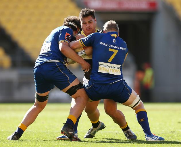Wellington's Alex Fidow is caught in the tackle of Otago players Josh Hill (left) and James...