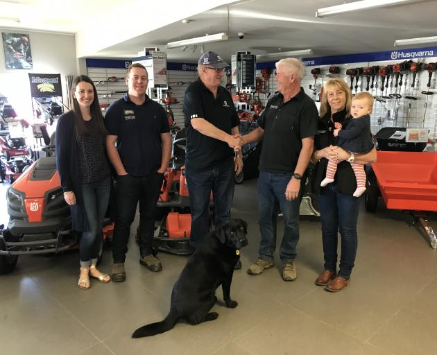 Malcolm Mead, centre, hands over the reins to Tony Brand and his family Emma, left, Simon, Kerin, Chloe and Roger the dog. Photo: Supplied