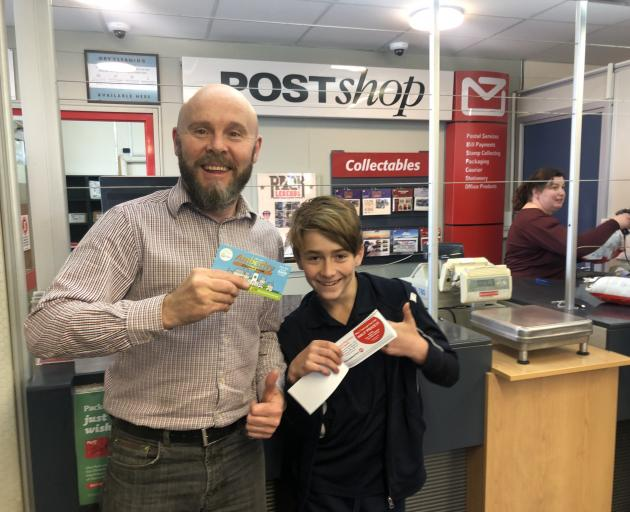 The new coupon book gets the thumbs-up from Brett Jones, owner/manager of the Amberley Post Shop, and Amberley School's head boy, Leo Bain. Photo: Supplied