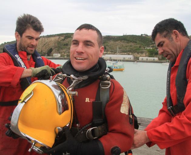 Bays Underwater Services crew members Sjors Hoogenboom (left) and John McLaren (right) assist Mr...