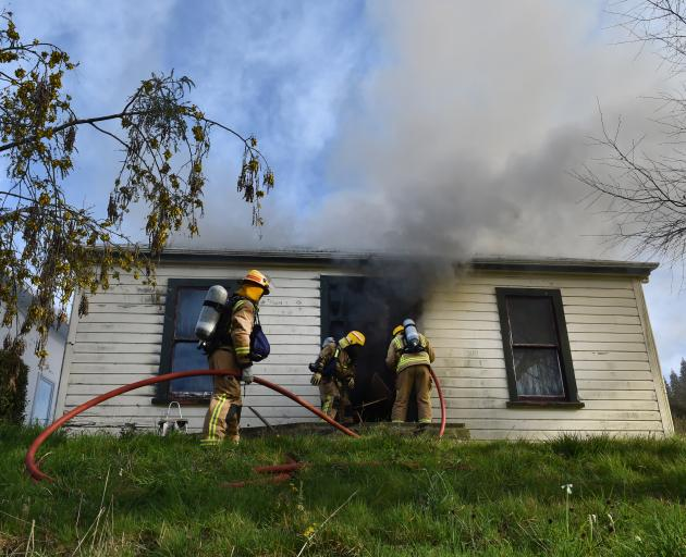 Firefighters get a hose into a burning home in Woodhaugh yesterday, after smashing the glass...