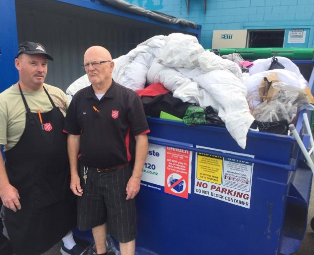 Salvation Army Family Store Hornby shop manager Terry Murray (right) and volunteer Neville Walton standing next to their overflowing rubbish skip filled with donated goods they cannot sell. Photo: Laura Hitchon