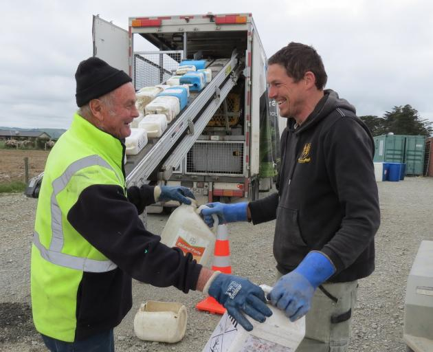 """Agrecovery contractor Rodger Gregge (left), of Ashburton, collects chemical containers from Kuana farmer John Officer, during the """"one-stop shop'' pilot rural waste management event at Limehills last week. Mr Gregge then put the containers on a conveyor b"""