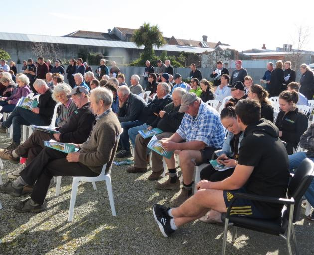 More than 100 people sit outside listening to Ministry for the Environment staff discuss the...