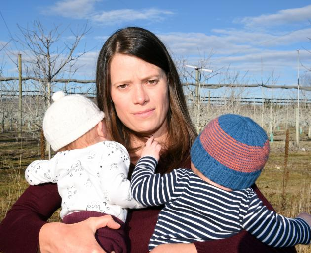 Katie Hill and her 3-month-old twins Chloe (left) and Zacon the boundary of her property near a noisy frost-fighting turbine. Photo: Gregor Richardson