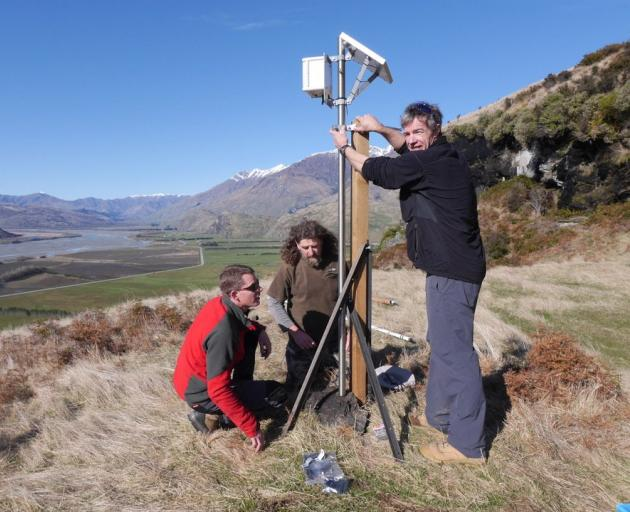 Simon Croft, Billy Barton (trapping manager) and Tim Sikma install a satellite trap aerial in the...