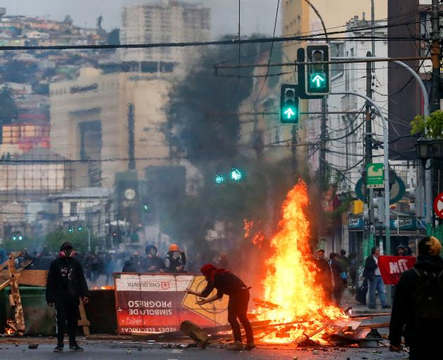 Demonstrators burn objects as they barricade a road during a protest against the government in...