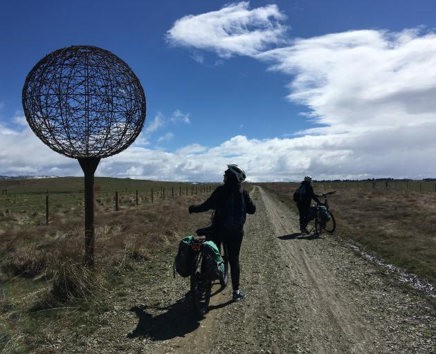 Cyclists admire a model of Jupiter installed near Wedderburn as one of nine planets in a scale...