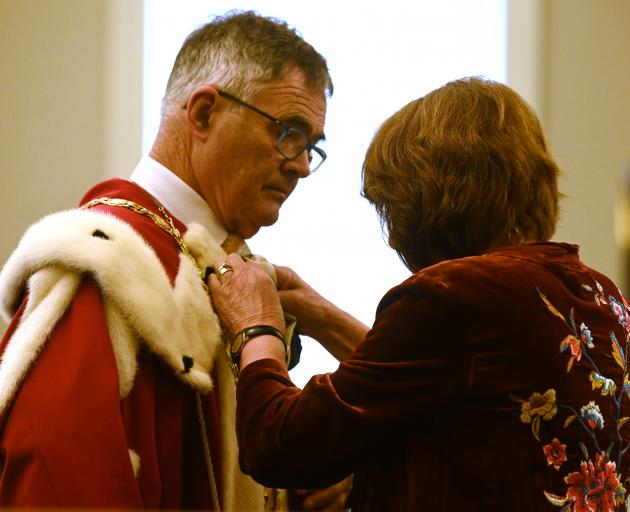 Dave Cull's wife, Joan Wilson, adjusts his robes. Photo: Linda Robertson