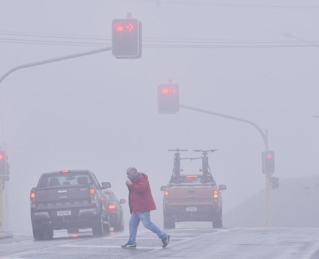 Drivers and pedestrians navigate their way through Dunedin's misty rain at the intersection of...