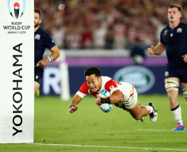 Kenki Fukuoka of Japan runs with the ball on his way to scoring a try during the second half of...