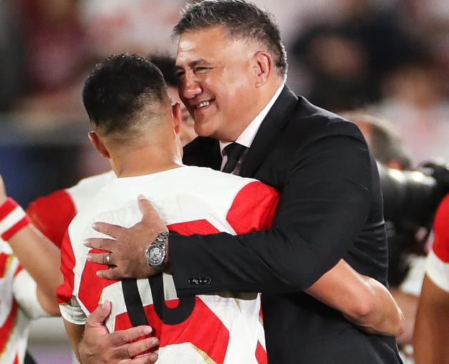 Japan head coach Jamie Joseph embraces one of the players, Yu Tamura, following the team's win...