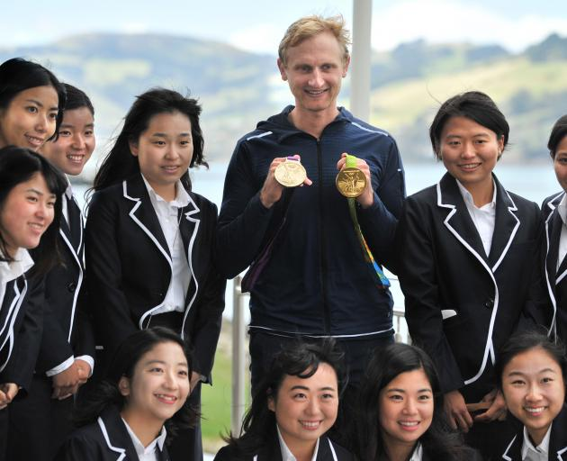 Bond displays his Olympic gold medals with members of the Keio University team.
