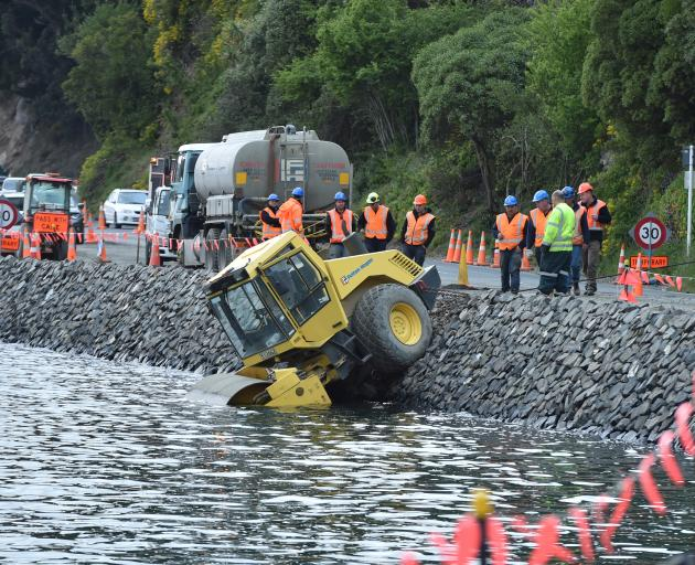 Fulton Hogan staff contemplate their next move after a roller ended up in Otago Harbour near the...