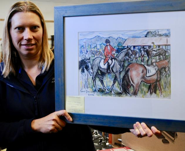 A 2004 watercolour by June Douglas is held by Kerryn Larwood, office administrator at the Bells Auction House in Kaiapoi. The painting is included in a large antique sale being held at the auction house on Wednesday next week. Photos: Shelley Topp