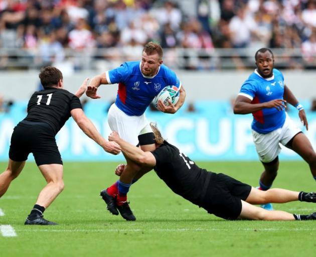 Namibia's Johan Tromp is tackled by Jack Goodhue and George Bridge during their Rugby World Cup...