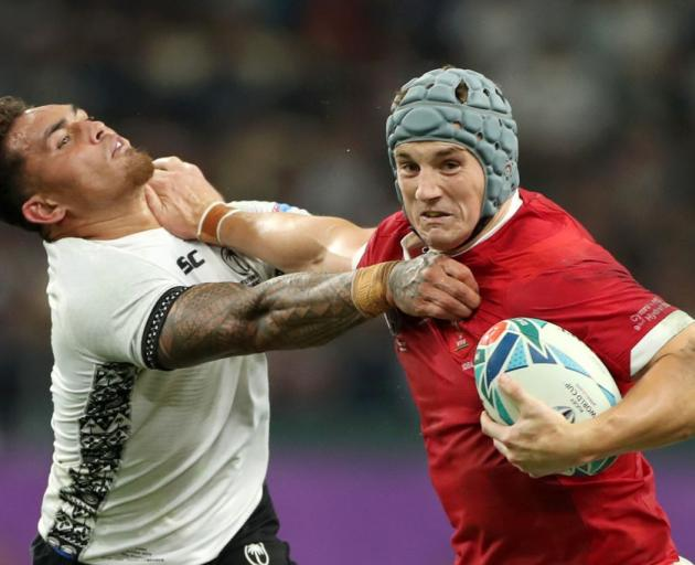 Jonathan Davies of Wales fends off Jale Vatubua of Fiji during their match last night. Photo:...