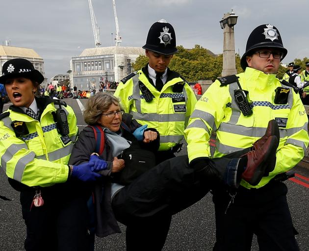 Police officers detain an activist at Lambeth Bridge during the Extinction Rebellion protest in...