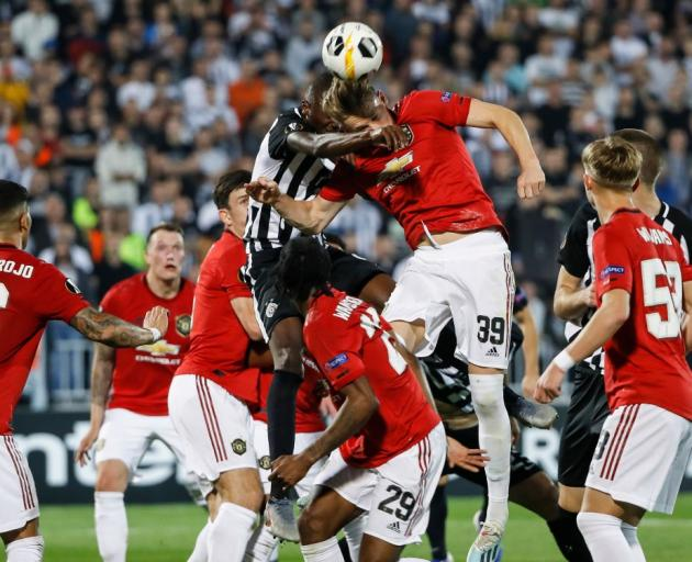 Umar Sadiq (left) of Partizan contests the ball against Scott McTominay (right) of Manchester...