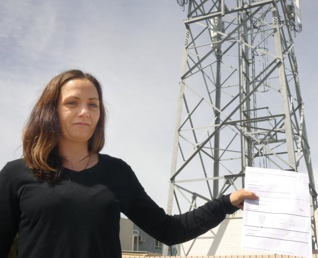 Alexandra woman Kelly Nyhon holds up a parliamentary petition she has launched opposing Spark's...