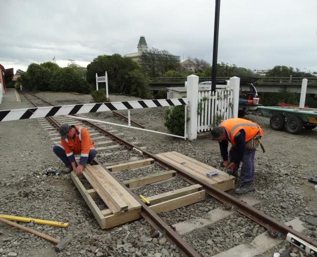 Waitaki District Council contractors construct a wooden footbridge over a section of the Oamaru Steam and Rail Society's track near Harbourside Station in Oamaru yesterday. Photo: Daniel Birchfield