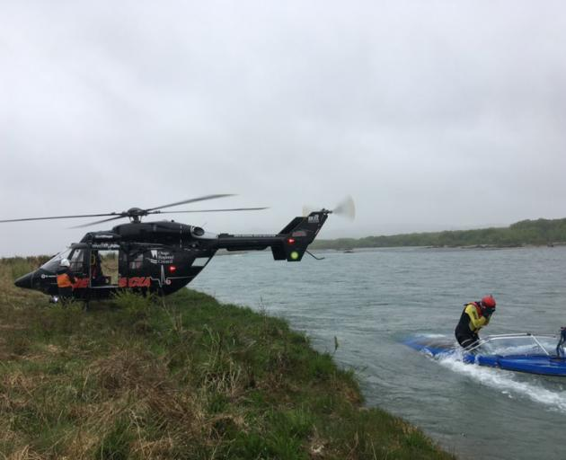 Rescue helicopter and search and rescue crew search the Waitaki River near Duntroon on Friday...