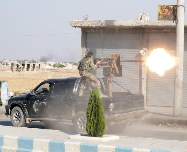 A Turkey-backed Syrian rebel fighter fires a weapon in the town of Tal Abyad, Syria. Photo: Reuters