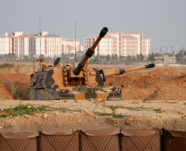 A Turkish army howitzer is positioned near the Turkish-Syrian border in Sanliurfa province. Photo...