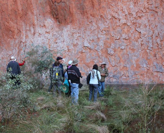 Tourists gather around traditional owner and guide Vincent Forrester at a water hole at the base of Uluru that is now polluted from human waste from climbers on the top of the rock. Photo: Kerrie Waterworth