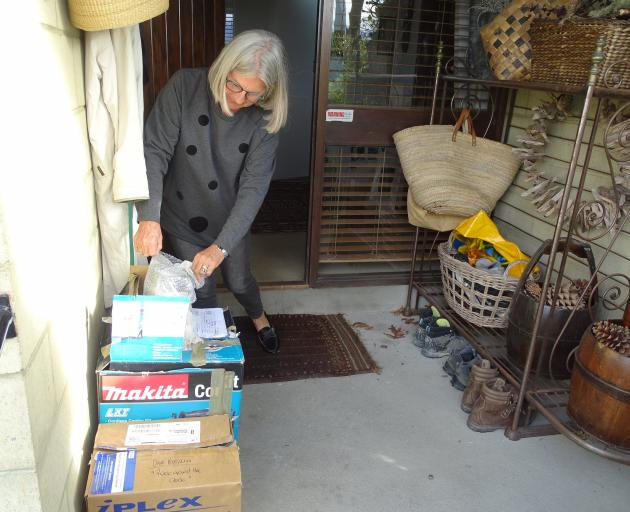 Committee member Jo Nimmo unwraps artworks delivered to the front door of president Vicky Fulton...