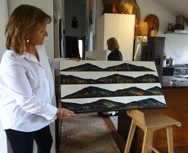 Wanaka Arts president Vicky Fulton holds one of the 200 works entered in this year's exhibition....