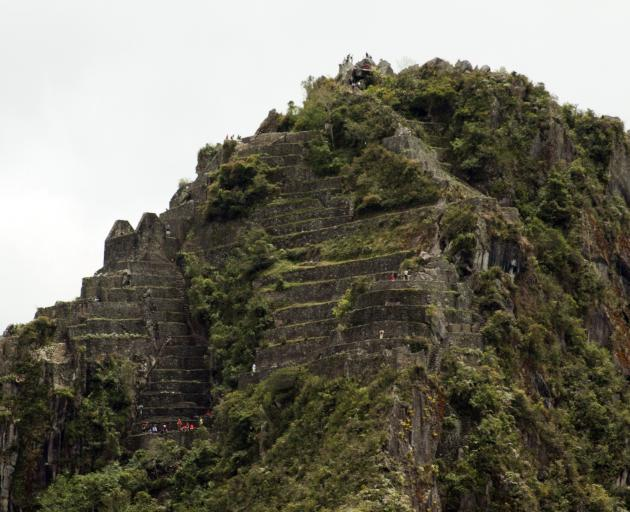 Some fit visitors to Machu Picchu climb steep steps to the top of Wayna Picchu, also known as...