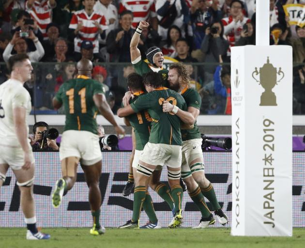 Cheslin Kolbe is enveloped by his teammates after scoring a late try that secured South Africa's...