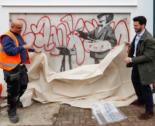 Men place a sheet over a Banksy mural known as The Painter, which first appeared in 2008, before it is officially unveiled in Notting Hill, London. Photo: Reuters